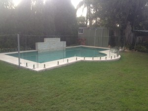A fence bounded by frameless pool glass fanecing